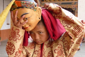 child monk putting on ritual mask